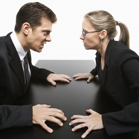 standoff: Caucasian mid-adult businessman and woman staring at each other with hostile expression.