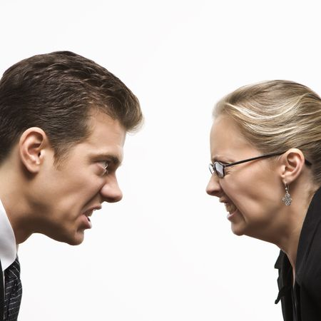 sexes: Close-up of Caucasian mid-adult man and woman staring at each other with hostile expressions.