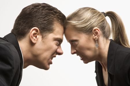 standoff: Caucasian mid-adult man and woman with foreheads together staring at each other with hostile expressions.