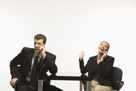 Caucasian mid-adult businessman and woman sitting and talking on cell phones. photo