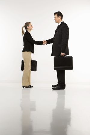 attache: Caucasian mid-adult businessman and woman shaking hands and holding briefcases.