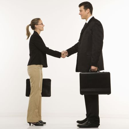 Caucasian mid-adult businessman and woman shaking hands and holding briefcases. photo