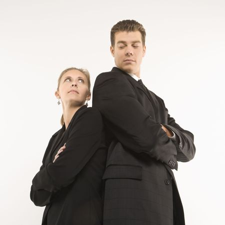 Caucasian mid-adult businessman and woman standing back to back looking at each other.  photo