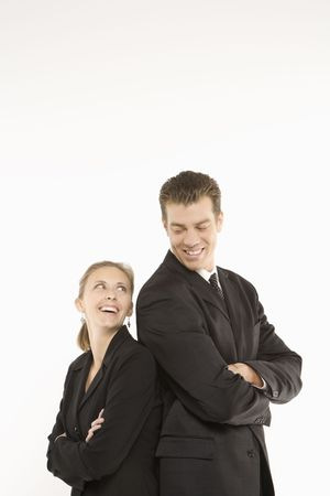 sexes: Caucasian mid-adult businessman and woman standing back to back and smiling at each other.