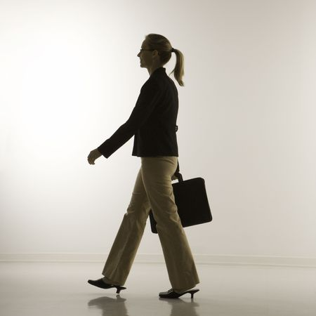 Silhouette of mid-adult Caucasian businesswoman walking and carrying briefcase. photo