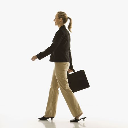Mid-adult Caucasian businesswoman walking and carrying briefcase. Stock Photo