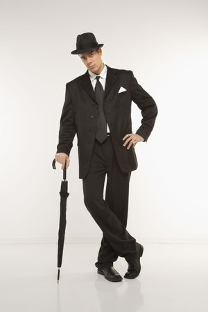 Caucasian mid-adult businessman wearing fedora leaning on umbrella and looking at viewer. photo