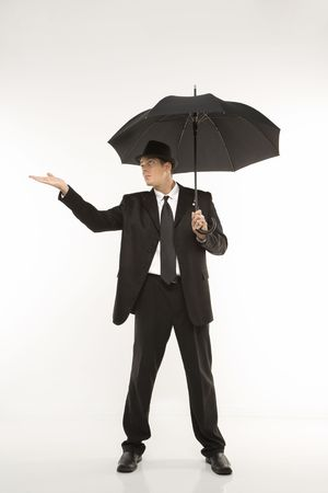 Caucasian mid-adult businessman wearing fedora holding umbrella with arm outstretched.