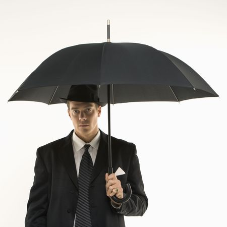 Caucasian mid-adult businessman wearing fedora holding umbrella  and looking at viewer. photo