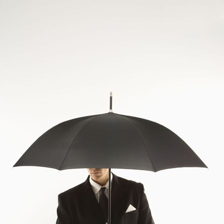 'hide out': Caucasian mid-adult businessman  holding umbrella with face covered.