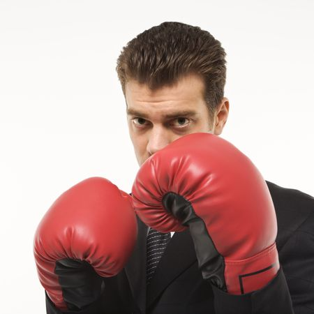 Caucasian mid-adult man wearing suit and holding boxing gloves close to his face. Stock Photo