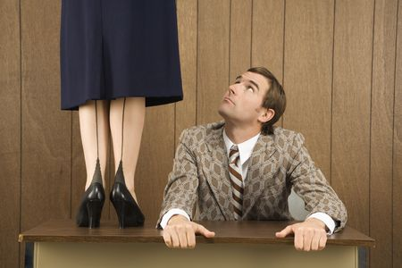 sexes: Mid-adult Caucasian male holding desk looking up to Caucasian female standing on desk.