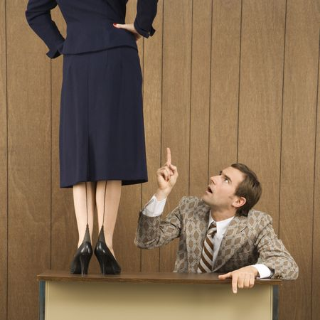 sexes: Mid-adult Caucasian male pointing up to Caucasian female standing on desk. Stock Photo