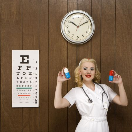 oversized: Caucasian mid-adult female nurse standing by wood paneling holding oversized pills and smiling at viewer.