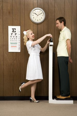 Caucasian mid-adult female nurse weighing man on scale. photo