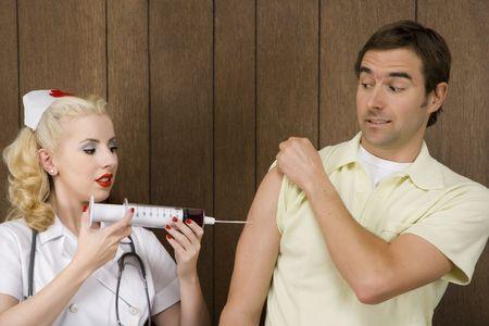 przewymiarowany: Caucasion połowy dorosłych kobiet pielęgniarka podający strzał do człowieka z przewymiarowany strzykawki.