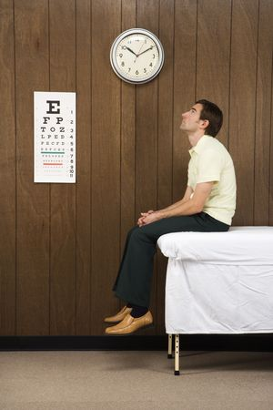 Caucasian mid-adult male waiting on table in retro doctor's office. Stock Photo - 1960546