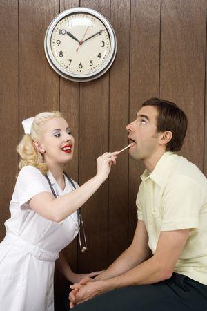 Caucasian mid-adult female nurse  examinating males mouth with tongue depressor. photo