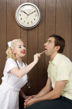 depressor: Caucasian mid-adult female nurse  examinating males mouth with tongue depressor. Stock Photo