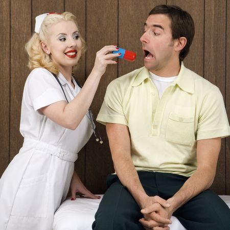 Caucasian mid-adult female nurse  giving mid-adult man giant pill. photo