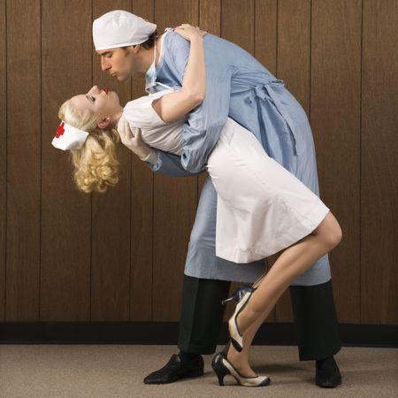 acoso laboral: Mediados de los adultos varones de raza cauc�sica cirujano flexi�n enfermera m�s apasionado hacia atr�s para abrazar.  Foto de archivo