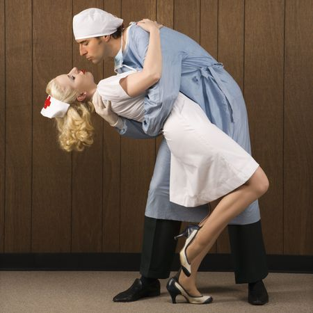 Mid-adult Caucasian male surgeon bending female nurse over backwards for passionate embrace. photo
