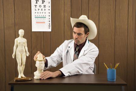 cappello cowboy: Met� degli adulti di sesso maschile caucasica medico indossando cappello cowboy seduto al tavolo a giocare con statuetta.  Archivio Fotografico