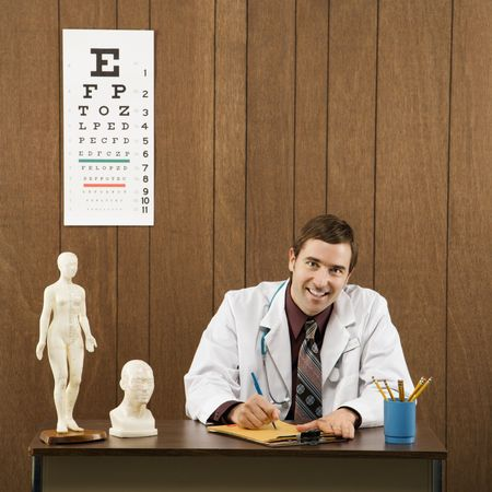 Mid-adult Caucasian male doctor sitting at desk writing and looking at viewer. Stock Photo - 1960433