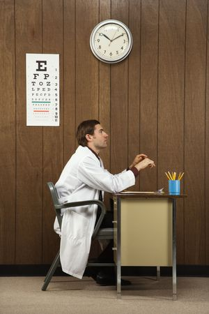 Side view of mid-adult Caucasian male doctor sitting at desk.  photo