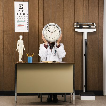 Caucasian male doctor sitting at desk holding clock over face. photo