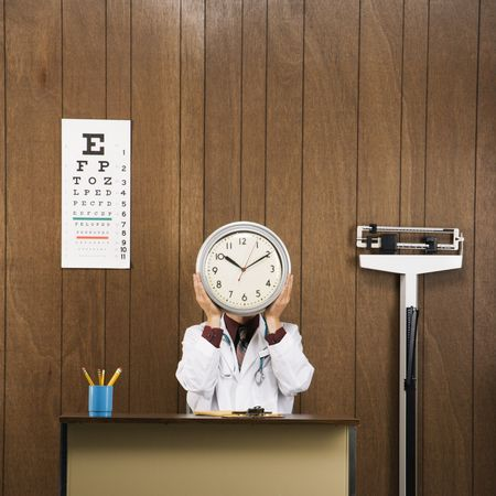 conceal: Caucasian male doctor sitting at desk holding clock over face. Stock Photo