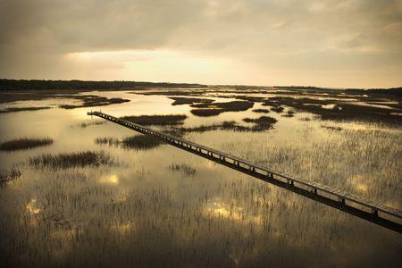 bald head island: Scenic wooden walkway stretching over wetlands at sunset on Bald Head Island, North Carolina.
