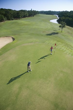 aerial photograph: Aerial view of mid adult Caucasian man and woman playing golf at Bald Head Island, North Carolina.