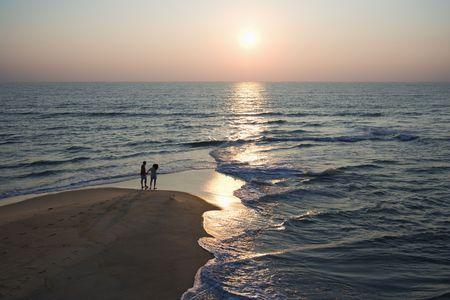 bald head island: Aerial view of couple on beach in Bald Head Island, North Carolina during sunset.