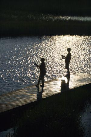 bald head island: Birds eye view of two teenage boys fishing from dock at Bald Head Island, North Carolina.