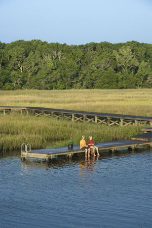 bald head: Aerial view of two teenage boys fishing from dock in marshy lowlands of Bald Head Island, North Carolina.