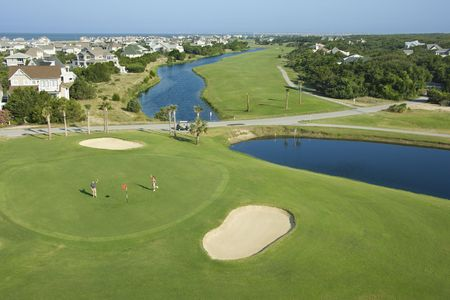 Aerial view of two people palying golf near residential community at Bald Head Island, North Carolina. photo