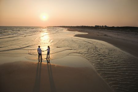 bald head: Aerial view of romantic couple standing on beach holding hands on Bald Head Island, North Carolina.