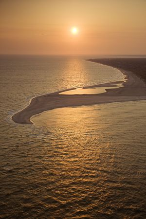 bald head island: Aerial view of sun over Atlantic ocean and shoreline of Bald Head Island, North Carolina.