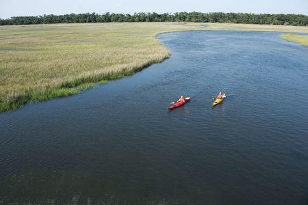 bald head island: Aerial of two teenage boys kayaking through marshland on Bald Head Island, North Carolina.