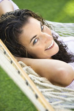 Portrait of pretty young adult Caucasian brunette female lying in hammock smiling up at viewer. photo