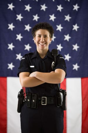 Portrait of mid adult Caucasian policewoman standing with arms crossed and American flag as backdrop smiling at viewer. Stock Photo