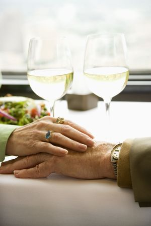 Close up of mature couple at restaurant table with womans hand resting on mans hand. photo