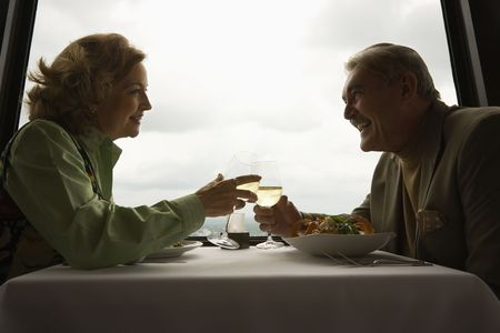 Caucasian mature couple at nice restaurant drinking wine and talking and laughing. Stock Photo