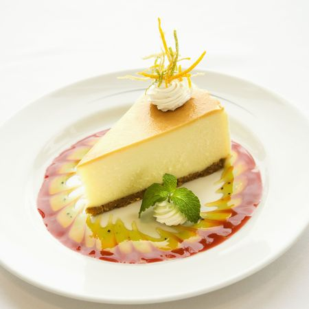 zest: Gourmet slice of cheesecake garnished with zest and sauce and mint sprig.