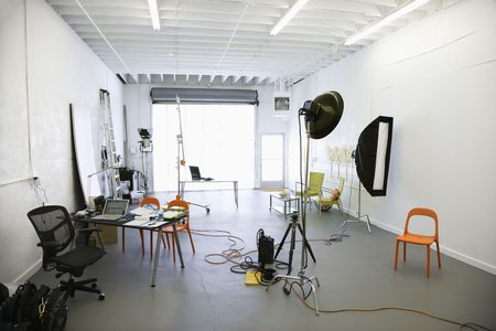 messy: Interior of  photography studio with lights and various equipment and props. Stock Photo