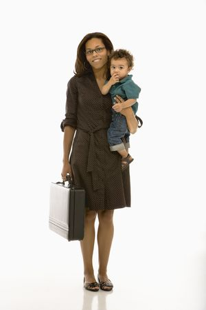 African American mid adult businesswoman holding toddler son on hip smiling at viewer.