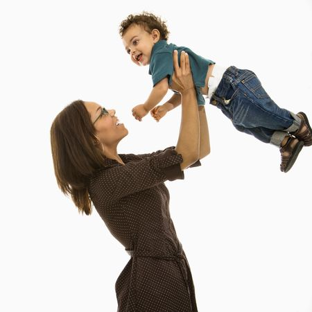 above head: Side view of mid adult African American mom lifting happy toddler son into air above head.
