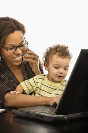 werkende moeder: African American medio volwassen zakenvrouw op het werk op de laptop en mobiele telefoon met toddler zoon op schoot.