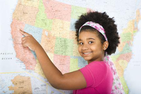 African American girl señalando el mapa de Estados Unidos y sonriente en espectador.